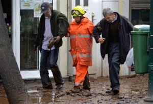 A man carries his shoe assisted by a firefighter as they walk down  a street covered with mud Sunday, Feb. 21 2010 in downtown Funchal, the  capital of Madeira Island. Rescue workers dug frantically Sunday to  free cars and homes buried under heaps of caked mud in Madeira, after  torrential...